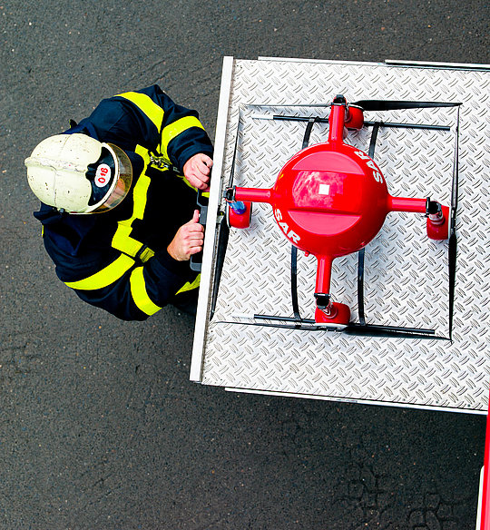 Fire fighter preparing a red Microdrones md4-1000 aircraft for the next emergency operation
