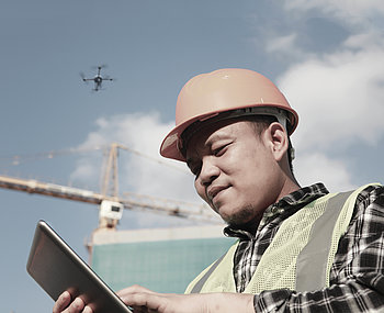 Specialist inspecting a construction site using a md4-1000 drone and a tablet.